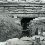 """n September 1968 we all were ordered to improved our assigned bunkers. RT Delaware went down to the old 4th inf compound 4 miles down the road and scrounged 8"""" beams and sacks of grenades. We Built this bunker with a Sand bag berm behind it. In every alert, senior officers would cluster there because of the protection."""