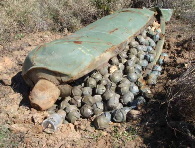 Unexploded BLU-26B cluster bomblets spilling out from a cluster bomb casing.