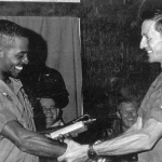 James, either receiving or presenting a SOG knife.