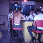 ED behind his bar in Tay Ninh. Notice Ray Charles up on the wall with cowboy hat and sun glasses appearing nightly