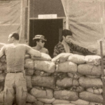 This is a photograph of Khanh Cowboy Doan taken in front of recon team Idaho team room in 1968 FOB 1 in Phu Bai. Cowboy is standing with RT Idaho interpreter Nguyen Cong Hiep - with sunglasses, and Spider Parks.