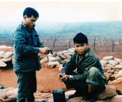Two of ST Tiger's Bru prepare their daily meal which included rice and rats. The parachute resupply drop being cancelled due to heavy ground fog.